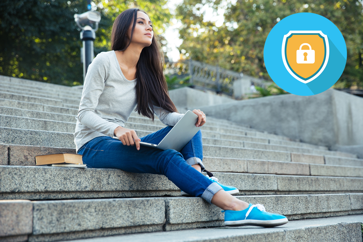 Female student sitting with laptop computer outdoors