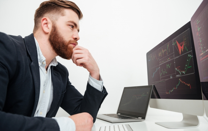 Serious businessman sitting and working with computer in office